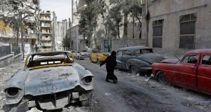 A woman walks past vintage cars parked outside the home of Mohammad Mohiedine Anis in Aleppo's  al-Shaar neighbourhood. Photograph: Joseph Eid/AFP/Getty Images