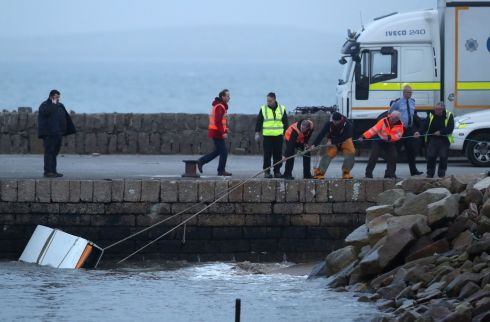 A piece of debris is dragged ashore, as the search continues for an Irish Coast Guard helicopter which went missing off the west coast of Ireland in the early hours of the morning. Photo : Brian Lawless/PA Wire