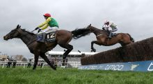 Sizing John ridden by Robbie Power jumps ahead of Djakadam on the way to winning the Timico Cheltenham Gold Cup. Photograph: Dan Sheridan/Inpho