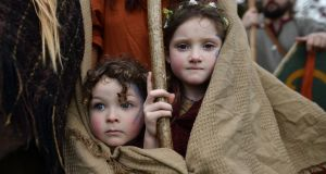 Forrest Bear Burns (L) and Willow Burns (R) huddle under their mother's shawl before they join their father, Marty Burns who plays the role of Saint Patrick, in the cross community Saint Patrick's Day parade on March 17, 2017 in Downpatrick, Northern Ireland. Photo by Charles McQuillan/Getty Images