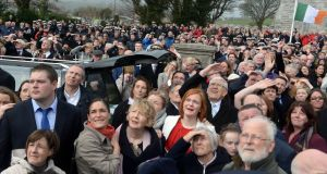 Funeral attendees look on as an Irish Coast Guard helicopter performs a flyover. Photograph: Cyril Byrne/The Irish Times