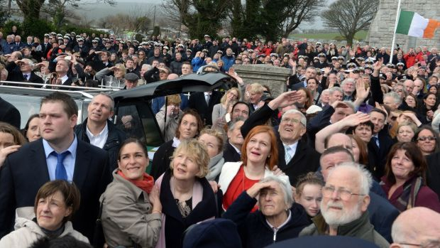 Attendees at the funeral look on as an Irish Coast Guard helicopter performs a flyover at the funeral. Photograph: Cyril Byrne/The Irish Times