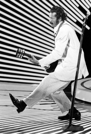 "Chuck Berry performing his ""duck walk"" as he plays his guitar on stage in April 1980. Photograph: AP"