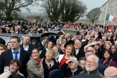 COMMUNITY MOURNS: Congregation watch a fly-past  by  an Irish Coast Guard helicopter on Saturday. Photograph: Cyril Byrne