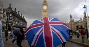 A pedestrian shelters from the rain beneath a Union Jack umbrella at the Houses of Parliament in London, following the pro-Brexit result of the UK's  referendum in June, 2016. Photograph: Justin Tallis/AFP/Getty Images