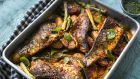Spicy harissa paste is used to coat a tray bake of fish and vegetables with wonderful results.