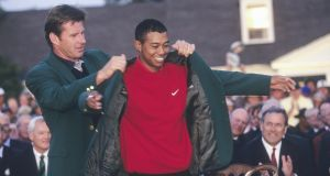 Nick Faldo puts the green jacket on Tiger Woods after the American's record-breaking win at the 1997 US Masters. Photo: Getty Images