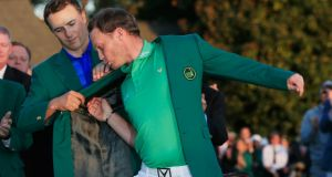 Danny Willett of England celebrates his victory last year as Jordan Spieth presents him the winner's green jacket. Photograph: Getty Images for Golfweek