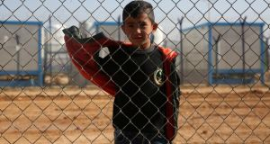 A boy stands behind a fence at Zaatari camp in Jordan, currently home to 80,000 Syrian refugees. Photograph: Sally Hayden