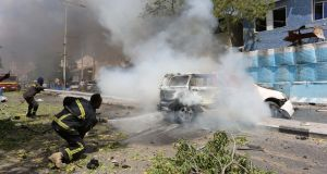 Firefighters extinguish a burning car at the scene of a previous explosion  in Somalia's capital Mogadishu on March 13th. Photograph: Feisal Omar/Reuters