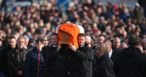 Martin McGuinness's sons, Fiachra (l) and Emmet, carry his coffin to his home in Derry. Photograph: Niall Carson/PA Wire