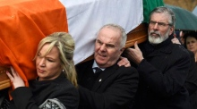 Gerry Adams and Michelle O'Neill carry Martin McGuinness's coffin through Derry