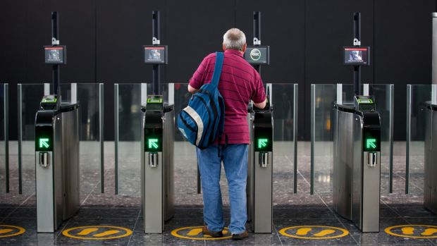 A passenger scans his boarding card in Terminal 2 at Heathrow Airport in London. The British Government has banned certain electronic devices on flights from certain Middle East countries following a similar move by the US authorities. Photograph: Andrew Cowie/EPA.