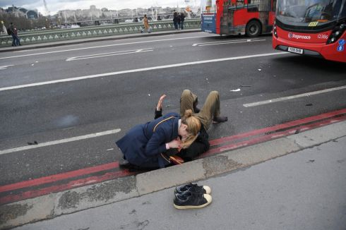 A woman assists an injured person after an incident on Westminster Bridge in London. Photograph: Toby Melville/Reuters
