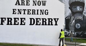 "A man paints the ""Free Derry"" corner wall in the Bogside on Wednesday ahead of the funeral of former deputy first minister Martin McGuinness. Photograph: Jeff J Mitchell/Getty Images"