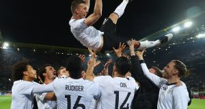Lukas Podolski is thrown in the air by his team mates after playing his last game for Germany in a friendly win over England. Photo: Alex Grimm/Bongarts/Getty Images