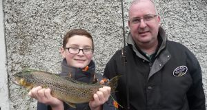 Gavin Maguire (11) with his dad and winning trout of 1.6kg at Tolka opening day