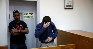 A US-Israeli teen (right) arrested in Israel on suspicion of making bomb threats against Jewish community centres in the United States, Australia and New Zealand over the past three months, before the start of a remand hearing in Rishon Lezion, Israel. Photograph:  Baz Ratner/Reuters