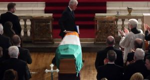 Former US president Bill Clinton touches the coffin during the funeral of former Northern Ireland Deputy First Minister Martin McGuinness in St Columba's Church Long Tower in Derry. Photograph: Niall Carson/AFP/Getty Images
