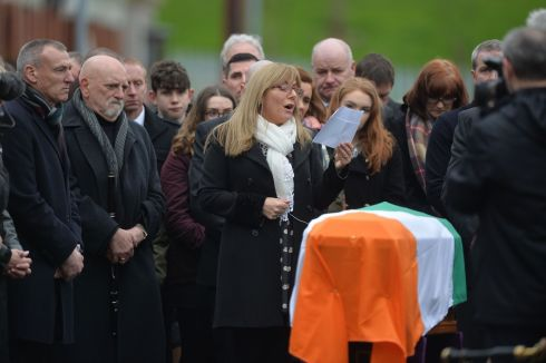 Frances Black sings besides the flag-draped coffin of Martin McGuinness outside St. Columba's Church.  Photograph: Alan Betson / The Irish Times