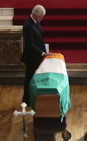 Former US President Bill Clinton touches the coffin during the funeral of Northern Ireland's former deputy first minister and ex-IRA commander Martin McGuinness.  Photograph: Niall Carson/PA