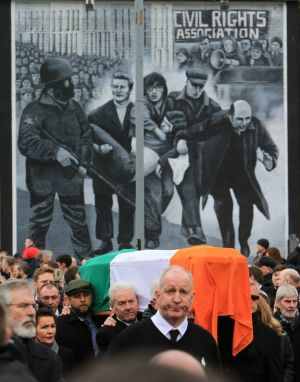 The coffin of Martin McGuinness is carried pass the 'Bloody Sunday' mural in Derry. Photograph: Paul McErlane/EPA
