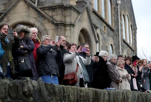 Members of the crowd watch the funeral cortege.  Photograph: Niall Carson/PA