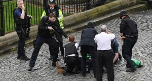 LONDON ASSAULT: A policeman points a gun at an injured suspect on the ground as emergency services work on him outside the Palace of Westminster, London. The suspect and a policeman who was stabbed died of their injuries, along with three others so far (at time of publication), in the terror attack. Photograph: Stefan Rousseau/PA Wire