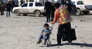 A displaced Iraqi man carries his belongings and pushes a child  after fleeing their homes due to the ongoing fighting between government forces and Islamic State (IS) on Saturday in Mosul. Photograph: AFP/Getty Images