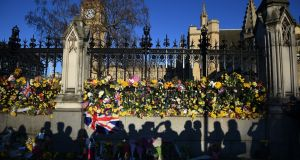 Shadows of member of the public are seen in front of  floral tributes next to the British houses of parliament in the aftermath of the  attack on Wednesday. Photograph: EPA