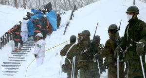 Firefighters carry a survivor they rescued from the avalanche in Japan. Photograph: AFP/Getty Images