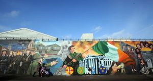 A woman with a pushchair walks past murals on Falls Road in 2017. Photograph: Paul Faith/AFP/Getty