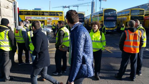 Two commuters walk by the scene at Ringsend garage this morning (Friday 31st Mar) as Dublin Bus workers stopped work in support of their Bus Eireann colleagues.  Photograph: Frank Miller / The Irish Times