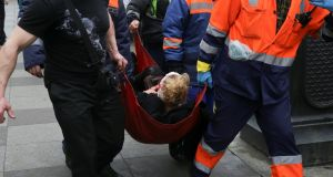An injured person is helped by emergency services outside Sennaya Ploshchad metro station, St Petersburg. Photograph:  Anton Vaganov/Reuters