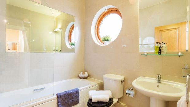 The bathroom has a rather smart round window that brings in a good deal of natural light