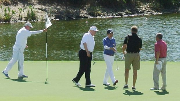 US president Donald Trump and Japan's prime minister Shinzo Abe (centre) playing golf in Florida in February. Photograph: JIJI PRESS/AFP/Getty Images