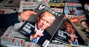 A woman holds a Chinese newspaper with a picture of US president Donald Trump at a news stand in Shanghai. Photograph: Getty