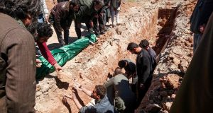 Syrians dig a grave to bury the bodies of victims of a a suspected toxic gas attack in Khan Sheikhoun, Idlib province, Syria, on Wednesday. Photograph:   Fadi Al-Halabi/AFP/Getty Images