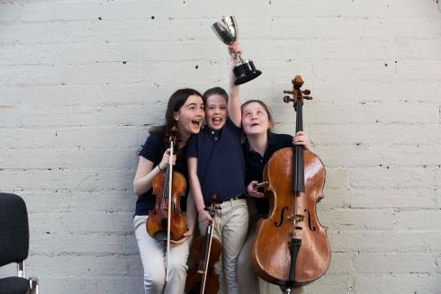 Sisters Chloe, Elena and Claire O'Connor of the Young European Strings Intermediate Orchestrsa admire the cup their Orchestra won for the 'Open Orchestra Competition'.