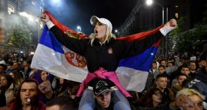 A protester waves the Serbian flag in front of the government building in Belgrade on Wednesday night. In a sign of growing ambition, protesters in the northern city of Novi Sad issued a list of demands. Photograph:  Andrej Isakovic/AFP/Getty Images