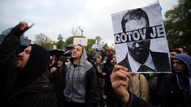 "Protesters hold an image of newly elected president Aleksandar Vucic with the words ""It's over"", in Belgrade, Serbia on Wednesday. Photograph: Koca Sulejmanovic"