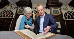 Amanda Bell, author of The Lost Book, and Jason McElligott, library keeper of Marsh's Library, Dublin. They are looking at the Galeni Librorum, a rare book that went missing from the library, which is at the heart of Bell's story. Photograph: Alan Betson