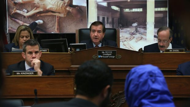 A Syrian Army defector in a blue hooded jacket during a briefing before the US House of Representatives foreign affairs committee in 2014. The defector, a former army photographer, has smuggled out of Syria more than 50,000 photographs that document the torture and death of thousands of Syrians in Bashar al-Assad's prisons. Photograph: Alex Wong/Getty Images