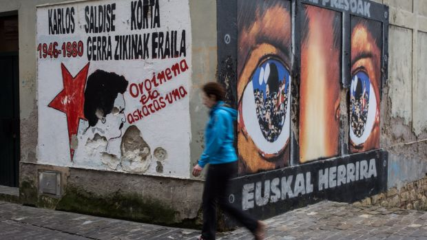 A woman walks past a wall with Eta graffiti in San Sebastian, Spain, in March 2017. Photograph: Javi Julio /Anadolu Agency/Getty Images