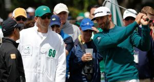 Dustin Johnson tests his swing next to his caddie Austin Johnson before pulling out of the Masters due to injury. Photograph: Reuters
