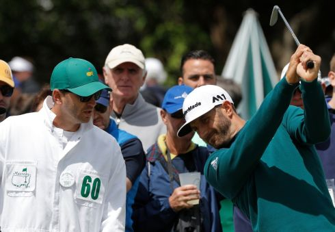 Dustin Johnson tests his swing next to his caddie Austin Johnson before pulling out of the Masters at the first tee. Photograph: Reuters