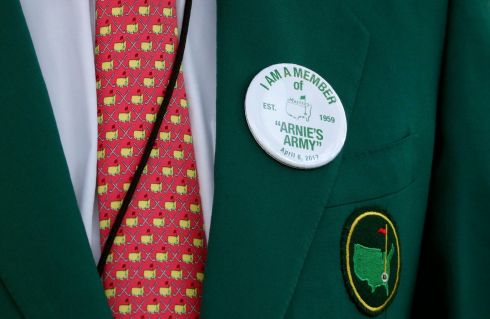 "A member wears an ""Arnie's Army"" badge in honor of the late Arnold Palmer during the ceremonial start. Photograph: Lucy Nicholson/Reuters"