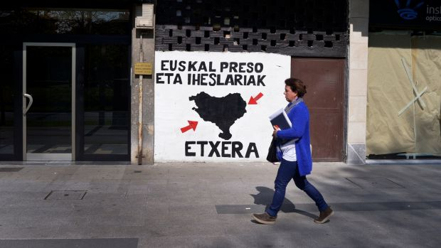 A woman walks past a mural in favour of imprisoned Eta members in the Basque town of Amorebieta, northern Spain, on Thursday. Photograph: Vincent West/Reuters