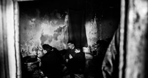 "A man cooking in one of the ""rooms"" in the abandoned warehouse in Belgrade that is home to about 1,000 migrants. Photograph: Szymon Barylski"