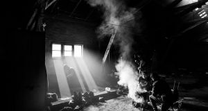 Men gather around a fire at the barracks during a meal. Photograph: Szymon Barylski